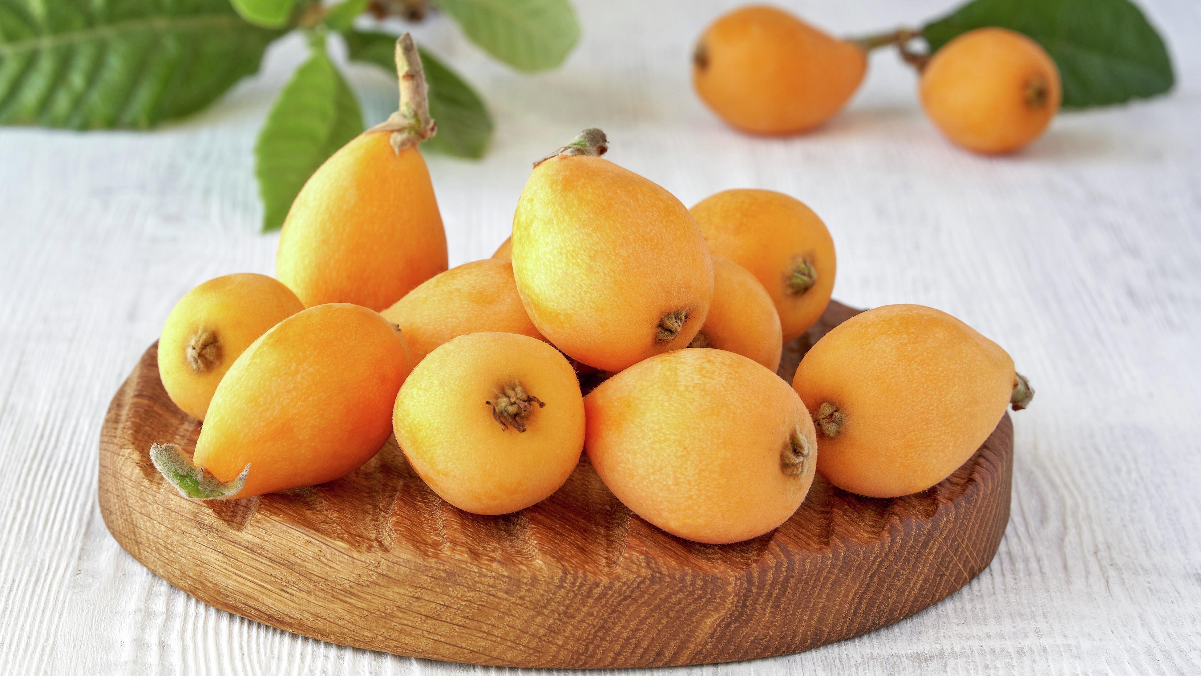 Orange loquat fruit on a wooden board