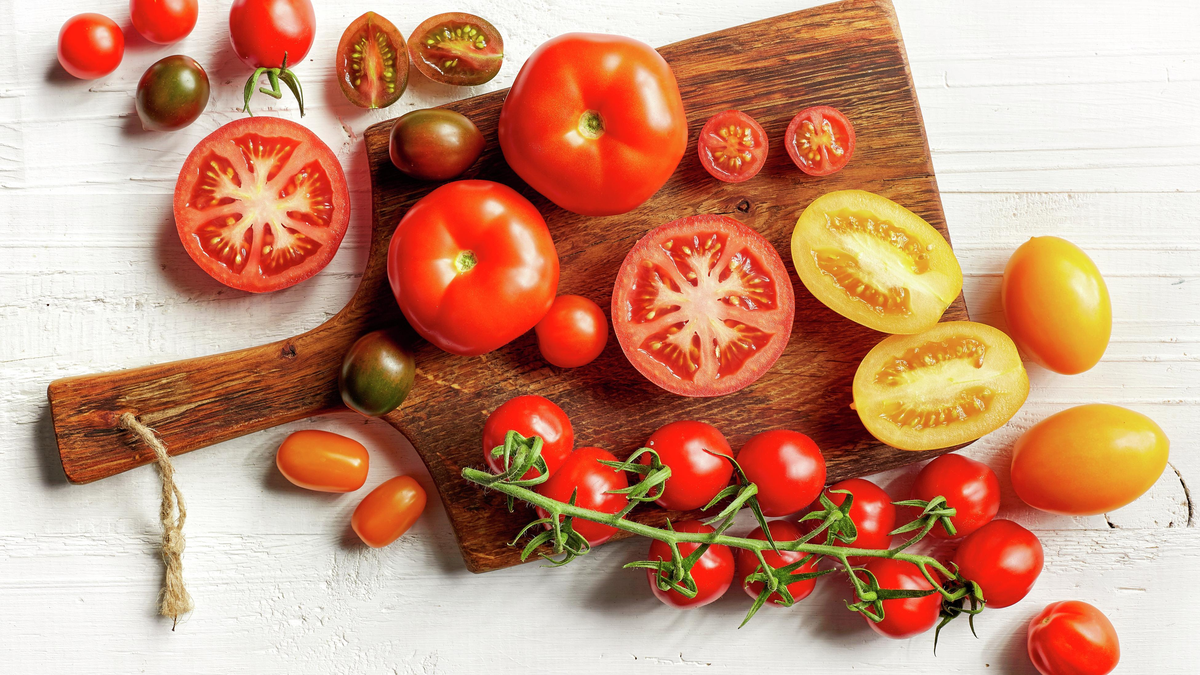 A variety of tomatoes on a chopping board