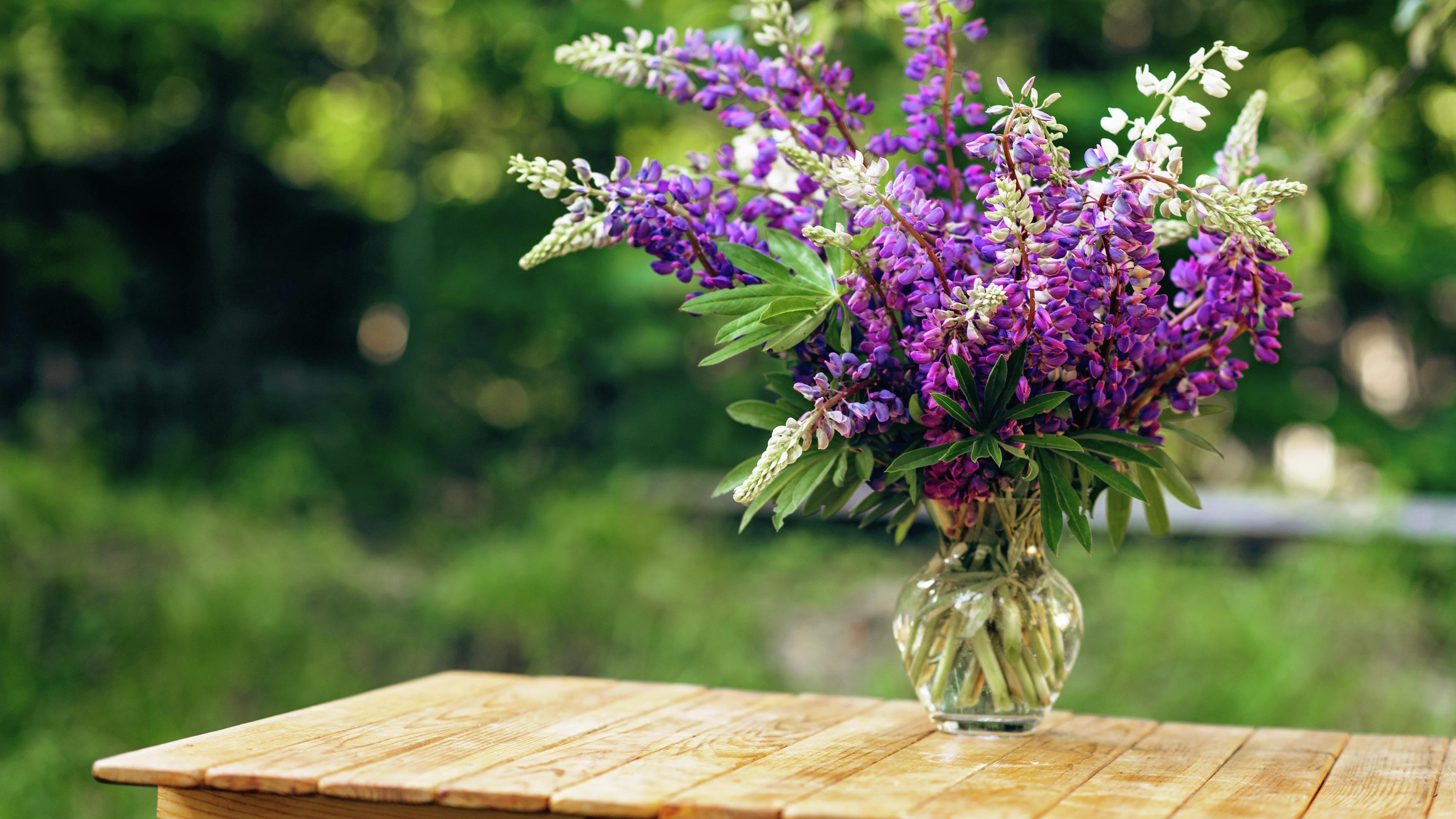 A vase of purple lupin flowers on a wooden outdoor table