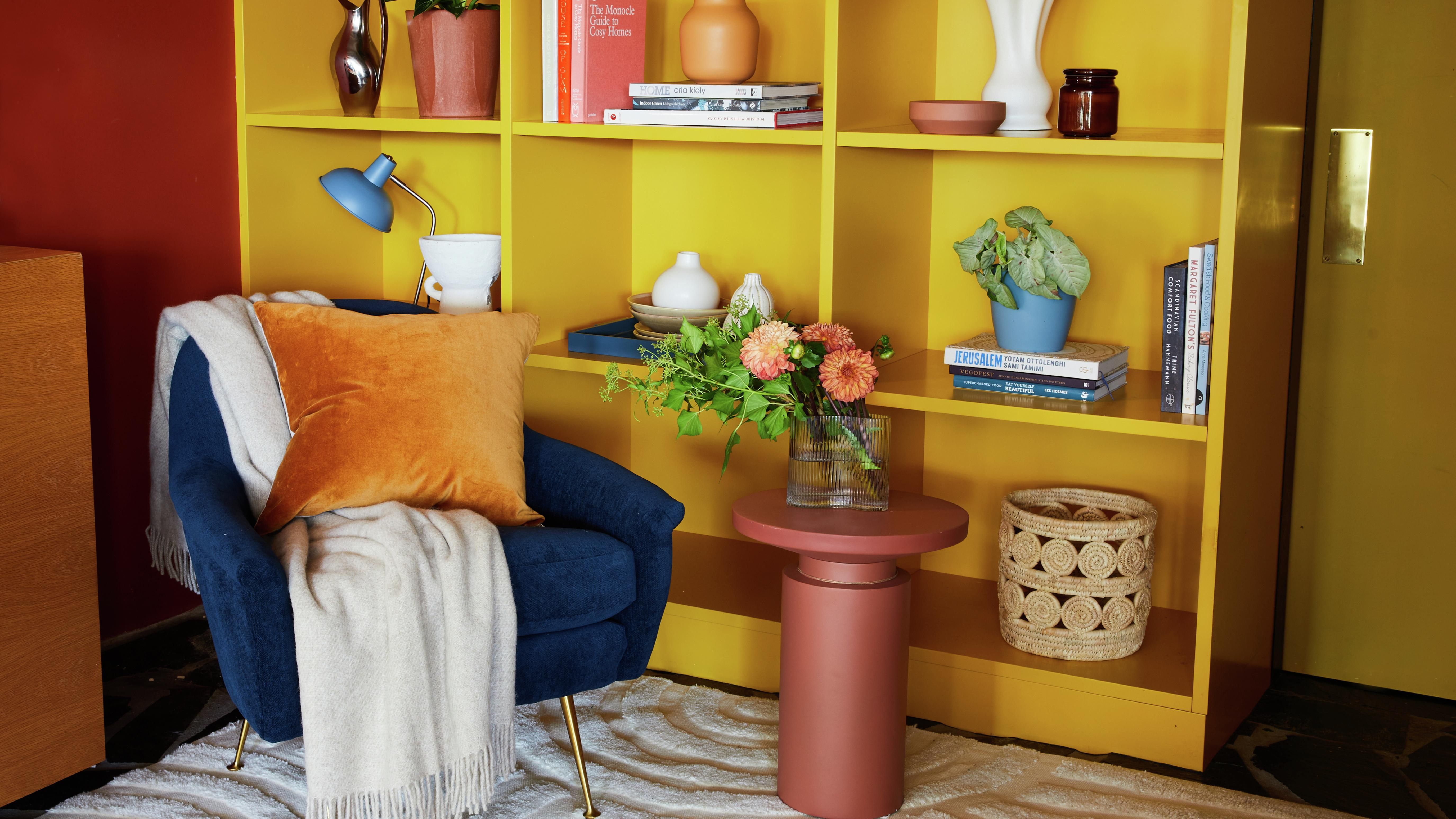 Vibrant reading corner including a bright yellow bookcase and a rich navy velvet armchair