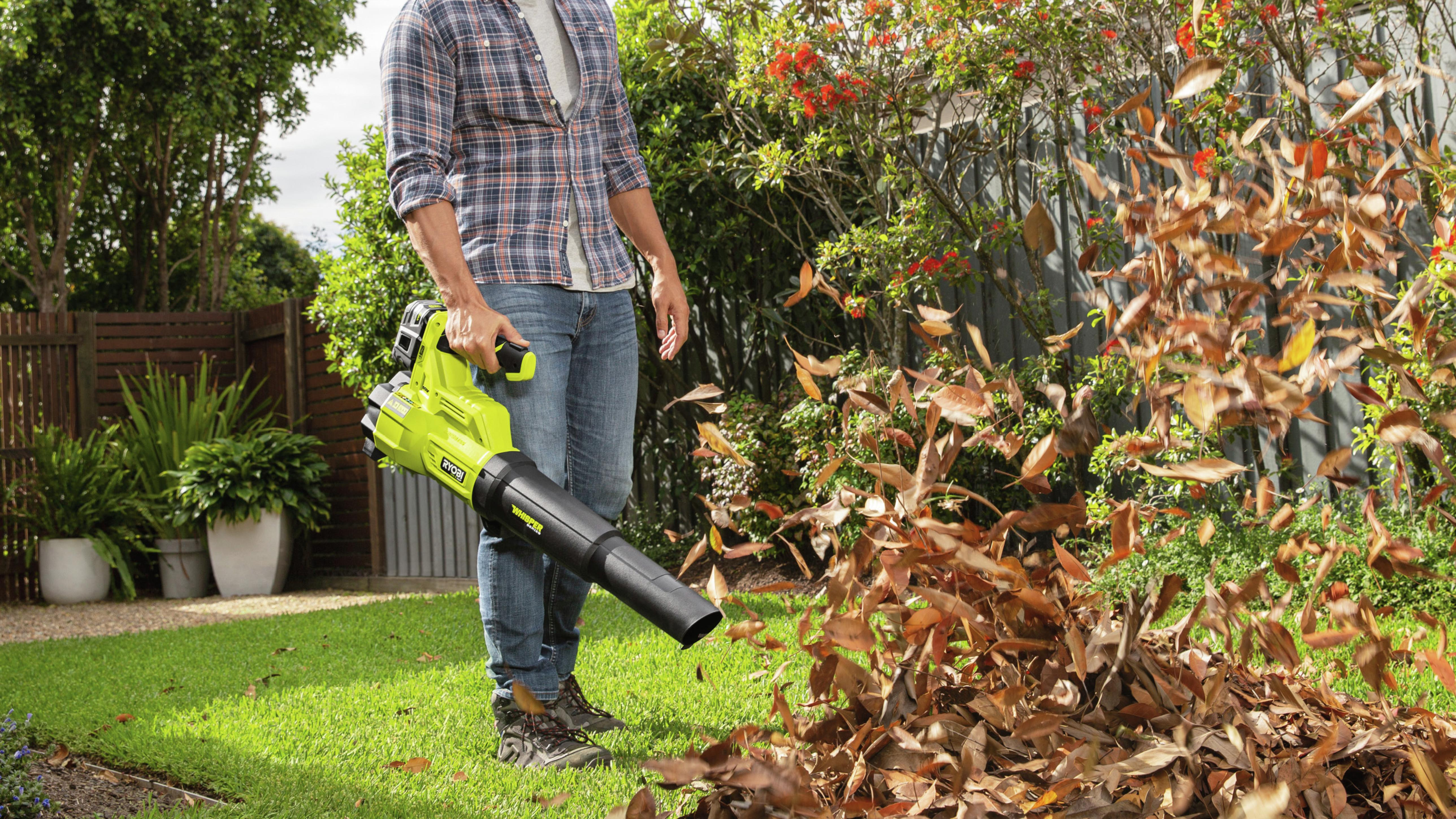 man using leaf blower in garden to move leaves